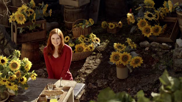 Amy Pond wearing a red sweater is smiling sitting in a yard filled with pots of sunflowers