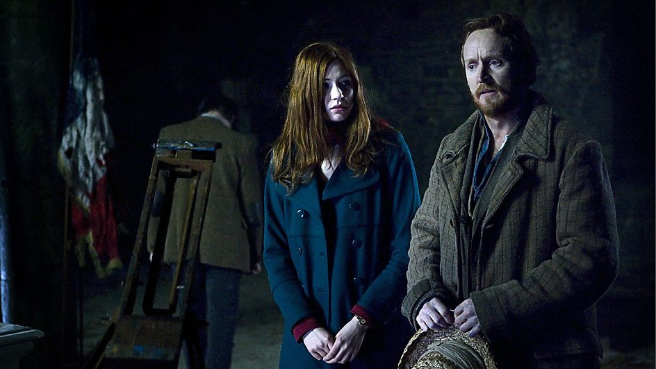 Vincent van Gogh standing in a field at night in wool coat, Amy Pond wearing blue coat looking at the artist sadly and thoughtfully. The Doctor's back is turned.